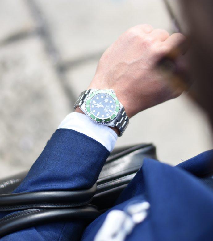 Bild einer Armbanduhr am Arm eines Mannes der nach der Uhrzeit schaut.