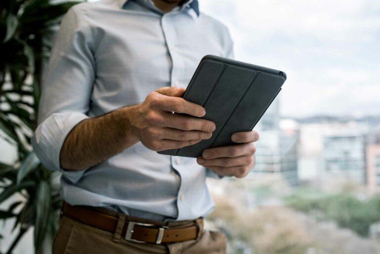 Bildausschnitt eines Mannes der ein Tablet in den Händen hält.