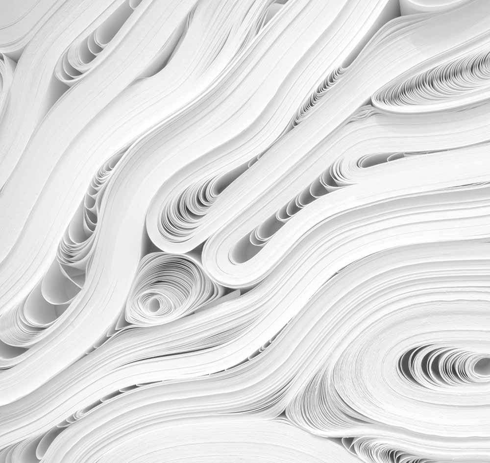 Zu sehen ist viel aufgerolltes Papier - Menger Engineering bietet Dienstleistungen rund um Anlagendokumentation