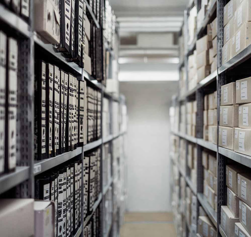 Zu sehen ist ein Archiv mit Ordnern - Menger berät Kunden zum Thema Dokumentenmanagement System